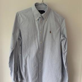Klassisk lyseblå/hvid stribet Oxford skjorte fra Ralph Lauren, dame model. Brugt meget lidt - fremstår som ny :)