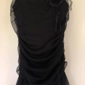 Sort stropkjole med flot asymmetrisk skørt og aftagelig blomst (monteret med brochenål). Kun brugt få gange, ingen brugsspor. Evt. TS-gebyr og fragt betales af køber.