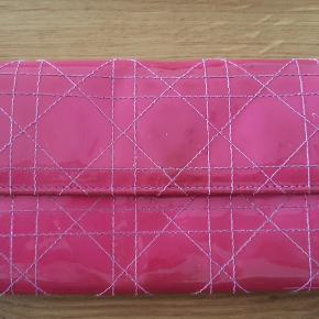 Christian Dior - Lady Dior - pung, pink, 100% ægte.  Pungen har: 12 kortrum, 3 rum til sedler og møntrum med lynlås. Tryklås lukning og Dior charms.  Størrelse: L=19 * H=10 * B=2 cm  Serienummer: 02-LU-1018  Pungen er brugt, men er stadigvæk pæn.  Kom med et bud!
