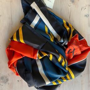 """Stort lækkert tørklæde (""""LIDAO"""") fra Malene Birger i den blødeste 100% silkekvalitet. Tørklædet måler 135 cm * 137 cm.  Tørklædet er blåt med gule skrå striber, og midt på tørklædet er der et orange felt, hvor der med sort står """"Ms Chief"""" (se billeder).  Tørklædet er aldrig brugt. Prismærke sidder stadig på.  Sælger kun og bytter ikke."""