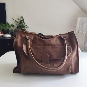 Adax læder taske i farven brun. Foran er der et stort rum med en lukker til. Indvendig er der både en lille lomme beregnet til mobil samt en lomme m. lynlås. Derudover medfølger en lille pung, der matcher tasken i læderet 🦔  Taskens mål:  Bredde 40 cm.  Højde 32 cm. Lille rum foran 28 cm.   Byd gerne kan både afhentes i Århus C eller sendes på købers regning 📮✉️