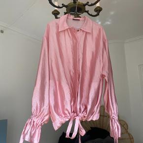 Yndigste skjorte fra Stine Goya. Desværre aldrig brugt. Den er stor i størrelsen/fittet og kan derfor bruges som oversize eller bindes ind i taljen. Der er snore i ærmerne, som enten kan bindes ind eller lade hænge.
