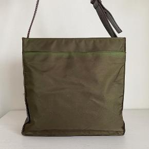 Lidt om tasken 👜 Prada crossbody taske i brun med en justerbar læderrem. Tasken kan holde computer hvor den dog vil stikke en smule op ad toppen.  Der medfølger desværre ikke noget til tasken   Stand 💬 Tasken er generelt i super fin stand, der er kun noget misfarvning ved stoffet primært i toppen samt enkelte ridser på læderet.   Autencitetsgaranti ☀️ Alle tasker autencitetstjekkes inden salg, vha. specifikke indikatorer på tasken som kan vise om den er ægte. Du kan derfor være tryg ved, at du investerer i et autentisk produkt!  Kun seriøse bud tak 🙌  Mængderabat gives ved køb af flere ting✨