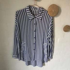 Rigtig fin blå og hvid stribet skjorte, med en sølv tråd i mellem hver stribe. Er næsten ikke brugt og fejler intet. Trænger dog til en strygning