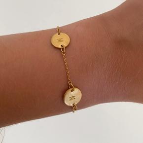 En lækker Love-tag armbånd fra Jane könig med bogstaverne M&N Standen er som den var helt ny: Ingen ridser, ingen skævheder. Armbåndet er nyforgyldt med 14 karat guld, så forgyldningen holder længe. Æske følger med Aldrig nogensinde brugt