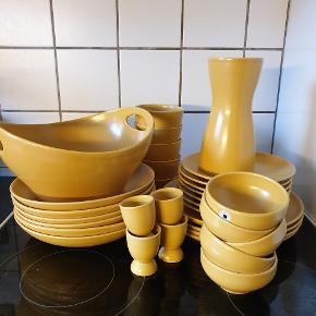 Höganäs keramik stel i gul BUD VELKOMNE  4 middagstallerkener  7 frokosttallerkener 6 dybe tallerkener 10 skåle (2 slags) 4 æggebæger Frugtskål Vandkande  Ingen skår eller lign.