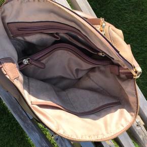 Flot taske fra Michael Kors i Rosa - på bagsiden er farven aftaget en anelse Taske er med flere indvendig rum, udvendig lomme, to hanke og aftagelig lang rem så den kan bruges over skulder 34 cm lang, 26 cm høj, 14 cm dyb Seriøse bud modtages  Bytter ikke