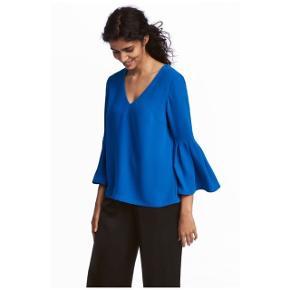 Flotteste blå bluse med trompetærmer fra H&M. Brugt et par gange. 100% polyester. V-hals udskæring foran. Ny pris var 200,-.
