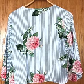 Mærket er Pigalle. Hvid med lyseblå striber og fine blomster. Brugt en enkelt gang. Prisen er + 34,95 i porto