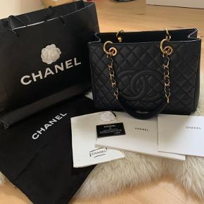 Overvejer at sælge min elskede Chanel Grand Shopping Tote ( GST), hvis rette bud kommer.  Tasken er af sort kaviar læder og guld hardware.  Tasken har jeg arvet af min mor, den er meget velholdt, som selvfølgelig ses på billedet. Tasken bliver desværre brugt alt alt for lidt.  Jeg er typen som altid passer rigtig godt på mine tasker. Det noget jeg har lært af min mor, da hun selv passer godt på hendes. Tasken bliver pudset og fyld op med silkepapir inden fra, så den ikke mister faconen, hver gang efter brug. Tasken er derfor meget velholdt, og standen er som ny, selvom den er fra 2012.  Der medfølger Chanel authentic kort, dustbag, Chanel blomst, den store sort Chanel pappose, Chanel klud, til at rengøre tasken, og alt det på billedet. Kvitteringen haves ikke længere.  Bytter ikke. Handler helst personligt. Tasken kan hentes og ses i Aarhus og omregnen. Ved TS handlen betaler køberen selv porto og gebyr.  Kan sendes flere billeder 🌸  Bud under 20.000kr ignoreres
