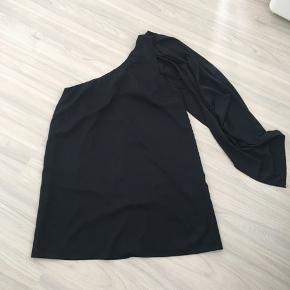 Den ene skulder er bar. Ved den anden skulder hænger et stykke sort stof.