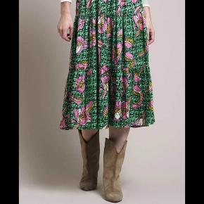 Nederdel med grønt og lyserødt mønster. Aldrig brugt.  Kan afhentes i Randers eller bringes til Aarhus.  Kan sendes på købers regning.