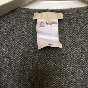 Blød trøje med knapper fra ' S Max Mara i 85% cashmere og 15% mohair. I god stand uden huller, pletter, fnuller eller lign. Mærket i nakken har lidt brugsspor , hvilket dog slet ikke ses når den er på :-) . Bælter medfølger. En str XL , men er nok nærmere en L. Tjek mål for en sikkerhedsskyld. Brystmål: 58 cm på tværs fra armhule til armhule, dvs 116 cm i omkreds + strech. Længde: 71 cm fra nakken og ned. Søgeord: lang cardigan bluse kashmir cashmere strik grå bindebånd varm knit.