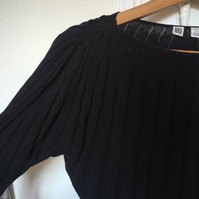 Pæn basic trøje med 'riller' i stoffet - fint , lige snit i kraven og lidt brede øverst på ærmet