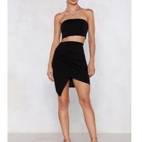 Lækkert sæt med nederdel og bandau-top i sort og elastisk materiale.