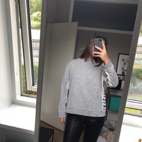 Sweatshirt fra mango med skriftdetaljer op ad armen samt ned af siden