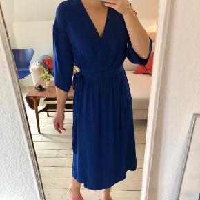 Slå-om midi kjole i smuk blå farve med 3/4 ærmer.  I rigtig god stand, kun brugt få gange. 100% polyester, der ikke krøller.   Kan også passe en str. M.  Mulighed for afhentning i Aarhus C 🌻🌻