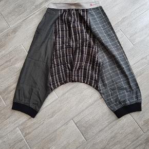 Et par anderledes, baggy og fede knickers fra Desigual. Bukserne er i forskellige typer stof med tern, ensfarvet og striber i sorte, grå, brune og sølv nuancer. Buksen sidder lavt på hoften og har hængerøv. Der er skrålommer i hver side og rib i benene forneden. Slutter under knæene og er fede til et par lange sorte støvler.
