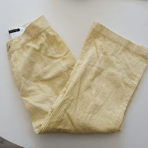 """Flotte lysegule bukser i fløjl fra Zara. Modellen er cropped med lige ben (se det sidste billede). Jeg købte dem herinde, og jeg har ikke brugt dem. Standen jeg købte dem i var 'næsten som ny', men jeg har valgt at sætte standen til 'god men brugt'. En af knapperne, som lukker buksen, ser ummidelbart ud til at være flyttet et par cm. Jeg ved det dog ikke med sikkerhed, og bukserne lukker fint, men se billederne. Den vil i så fald nemt kunne flyttes længere """"ind"""".   Jeg sælger også tilhørende blazer, se særskilt annonce på min profil 😊"""
