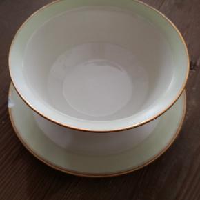 Royal Copenhagen smuk sovseskål med to skår, derfor prisen. Lille brun plet i keramikken indeni. Antik skål i mint, hvid og guld. Kan evt. repareres, så den bliver fin igen. Diameter nederst 21 cm, øverst 16 cm.