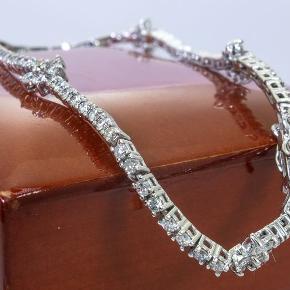 Sælger denne smukke 1.77 carat Tennis Brillant/Diamant armlænke i 14 K Hvid Guld med Certifikat. Armlænken har dobbelt sikkerhedslås og er helt nyt.  Vejl. butik-pris: ca. 35.000 kr  Diamant info: Diamant vægt: 1.77 carat Diamant Farve: F-K Diamant klarhed: SI Diamant Form: Runde Brillanter Diamant antal: 108 stk. Armlænke guld vægt: 5,8 gram Armlænke længde: 18 cm  Medfølger original certifikat og smykke æske.