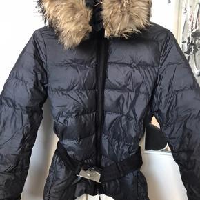 Smuk jakke fra Moncler med bælte med spænde på og smuk pels. Sender gerne flere billeder ved seriøs interesse. Str 1 Lynlåsen kan godt drille lidt men fungerer stadigvæk som den skal