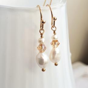 Hjemmelavede øreringe med små ferskvandsperler og champagnefarvede krystalglasperler på rosaguld kroge.  Fuld længde er 2,7 cm. Fast pris. Æske kan tilkøbes for 5 kr. Kan også sendes som brev for 10 kr.  Se også mine andre annoncer med smykker 🧞♀️