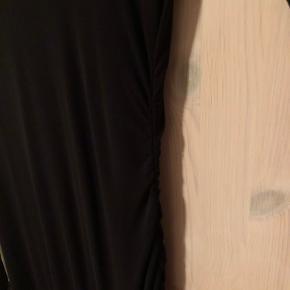 Flot kjole med anderledes snit. Skåret skråt forneden og draperet/ rynke effekt i siden. Lille kig til ryggen og v- udskæring foran.  Vasket 1 gang.