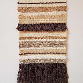 Unika håndlavet vægtæppe vævet af genbrugsgarn.  Måler 31 x 58 cm inkl. ophæng og frynser.