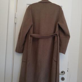 Flot, lang frakke fra Zara i str S i en flot minkfarve. Fejler intet og er ikke nusset i stoffet eller har huller. Med bindebælte i taljen