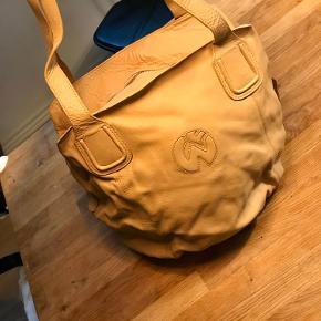 Fik tasken i gaven, men har aldrig brugt den. Tasken er i læder og indvendigt er den polstret med fint blomsterprint. Der er lige plads til iPad'en eller computeren.