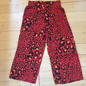 Vide bukser fra Gestuz i rød leopard med elastik k livet. Passer både m og L - stort set ikke brugt og har ingen fejl.