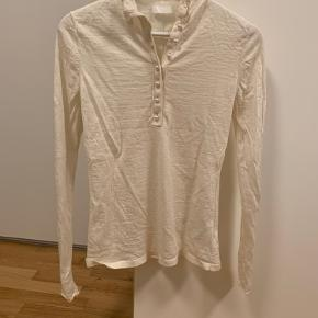 Fin bluse fra H&M, er kun prøvet på og derfor som ny. Der er en ekstra perle med til, hvis en af perlerne skulle falde af. I siden er der en blondestribe på begge ærmer