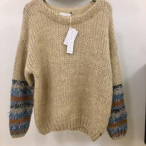 Handknitted sweater w. volume in mohair quality. The sweater features long sleeves and o-neck. The sweater has some fine colorful details w. lurex at cuffs.