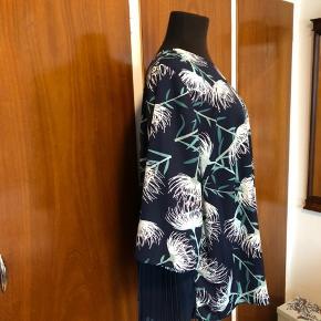 Smuk blå bluse fra Anyway Copenhagen med blomstermønster og plisseret stykke på den nederste halvdel af ryggen. Den er helt ny med mærker. Str.50/52. Polyester Mål: Str.50/52: Bryst 69cmx2 Talje 69cmx2 (mere plads pga plissering) Længde 71cm Sender gerne:) Til salg flere steder