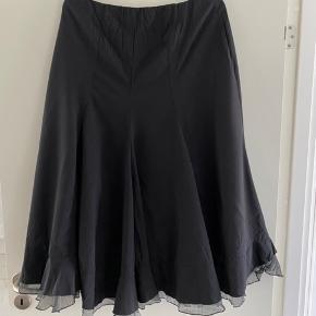 """Smuk og anderledes nederdel med fine detaljer. Har et lidt """"krøllet"""" look samt detalje nederst med kontrast """"flæse"""" med sølvstræjf i.  Er lavet af 45% Nylon og 55% polyester. Taljemål 40 cm. (Kan give sig en anelse) Længde ca. 75 cm. fortil og ca. 83 cm. bagtil. Er i rigtig fin stand."""