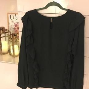 Varetype: Bluse - langærmet Farve: Mørkegrøn Oprindelig købspris: 450 kr.  Fin let Ichi bluse i mørkegrøn/flaskegrøn med flæser både foran og bagpå og en knaplukning bagpå.  Den er kun blevet brugt en gang, da den desværre ikke matchede det andet grønne tøj jeg havde købt den til.  Se også mine andre annoncer her på Trendsales fra bl.a. Odd Molly, Selected femme, Creton, Karen By Simonsen.