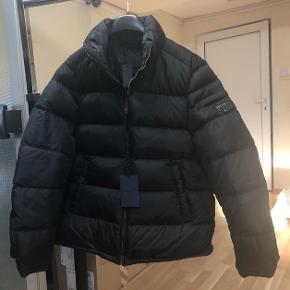 100% authentic PRADA JACKET color: black Size: 52 Reference number: SGY091 Two outer side pockets Triangle metal logo on the sleeve Front zip fastening Without hood