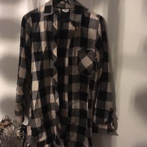 """Super fed, sort/grå/hvid ternet, lang skjorte/skovmandsskjorte i str S, fra mærket """"Anti blue"""", købt i London for hvad der svarede til ca. 300 kr. Ærmerne kan """"bindes op"""", så de bliver kortere. Normal i størrelsen, aldrig brugt, med brystlomme.   Hvis den skal sendes, betaler køber fragt.   Mvh Betina Thy"""