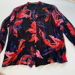 Flot skjorte i lækre farver på en sort bund. Kinakrave og metal knapper. Brugt 4-5 gange.