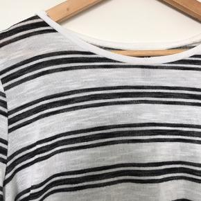 En fin stribet bluse fra H&M med dybe slidser i siderne og en runding foran og bagpå.