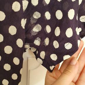 Sød kjole fra Ganni. Stoffet under ærmer har fortrængt sig, hvilket ses på prikkerne (se billede) sælges derfor billigt. Bindes med brede bånd om taljen.