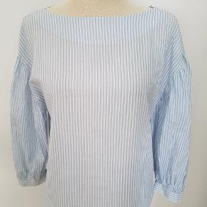 Helt ny med mærke 🌸  Sød blå og hvid stribet bluse i ren bomuld med lidt ballonærmer og en åbning i ryggen.
