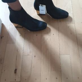 Smukke sorte støvletter i ægte læder med firkantet snude og hæle med guldfarvet metal. Skal såles hos skomager inden de kan bruges (billig udgift).  Nypris: 599,- Pris 250,- - eller byd i kommentarfelt.