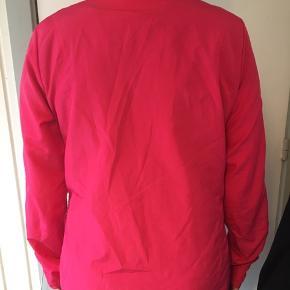 Pink og sort løbejakke fra Adidas med to lommer foran.