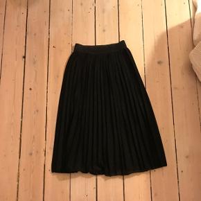 Lang sort plisseret nederdel, med en anelse glimmer i