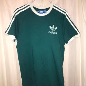 Adidas t-shirt i M i den lækreste grønne farve (du kan se billederne med/uden blitz) - tag den til kun 75 kr! Den er ikke oversize, heller ikke stram - men en god mellemting.