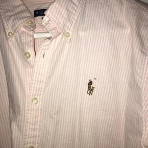 Lækker lyserød/hvid stribet skjorte fra Ralph Lauren i en str. 12, som svarer til en M-L. Nypris: 700kr  Der er 2 pletter på, som vist på billederne