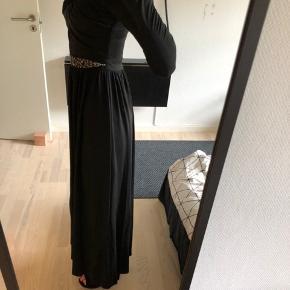 """Fin gallakjole fra Little Mistress str. 34 købt på ASOS i slutningen af 2015.  Med lange ærmer, hvilket gør den behagelig i den koldere tid - det er en varm kjole, som kan anbefales hvis man har tendens til at fryse ☀️ Med """"hul"""" i maven og fint perlebånd som udsmykning. Virkelig god pasform, sidder tæt ind til taljen. Har en lille slids i det ene ben også. Flere billeder er lagt op i kommentaren."""