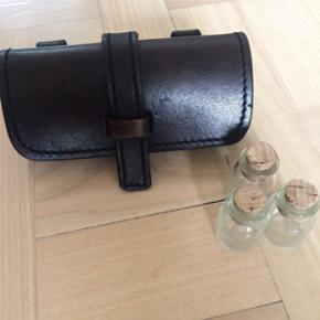 Eliksir taske i læder til rollespil og leg. Til at sætte fast i et bælte. Med tre små glasflasker med korkprop. Som ny. Nypris 200 kr.